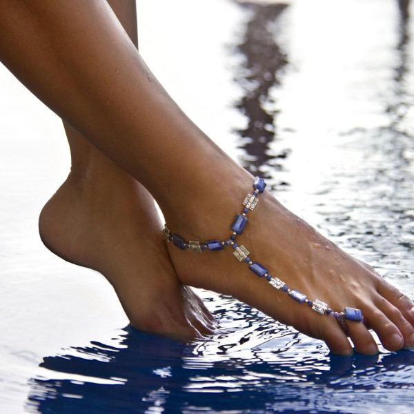 Female feet above the water with bracelet on ankle
